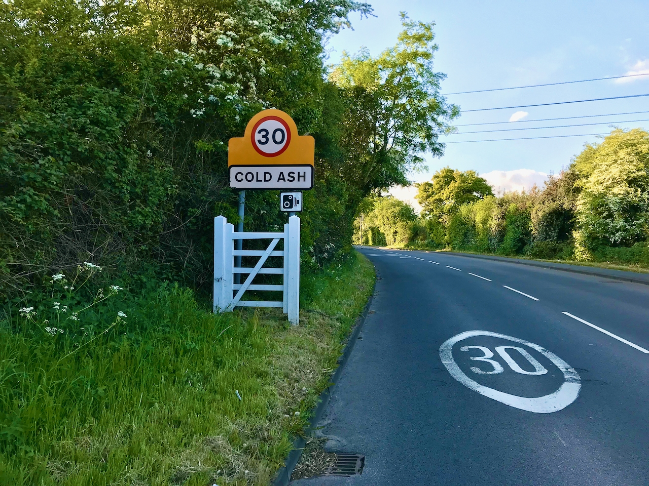 "A roadway with a small white gate on the lefthand side. A road sign above the gate reads ""Cold Ash""."