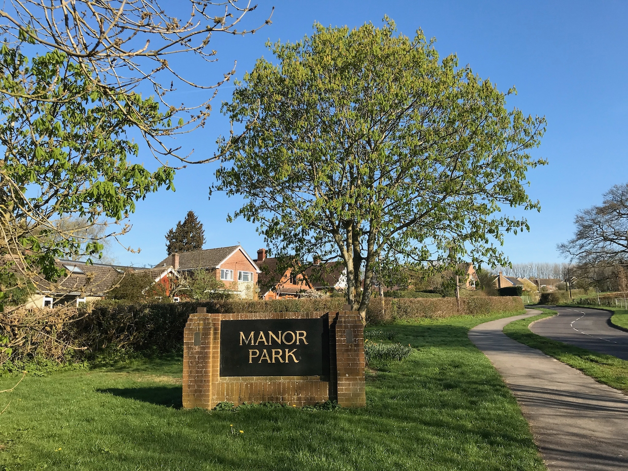 "A sign reading ""Manor Park"" sits beside a footpath and a large tree."
