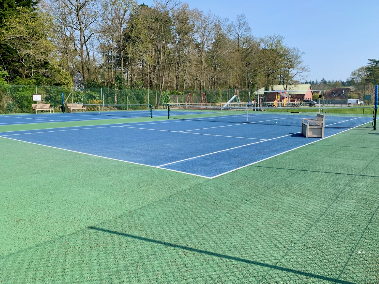 Two blue tennis courts with green tarmac surround. The Acland Hall can be seen in the background.