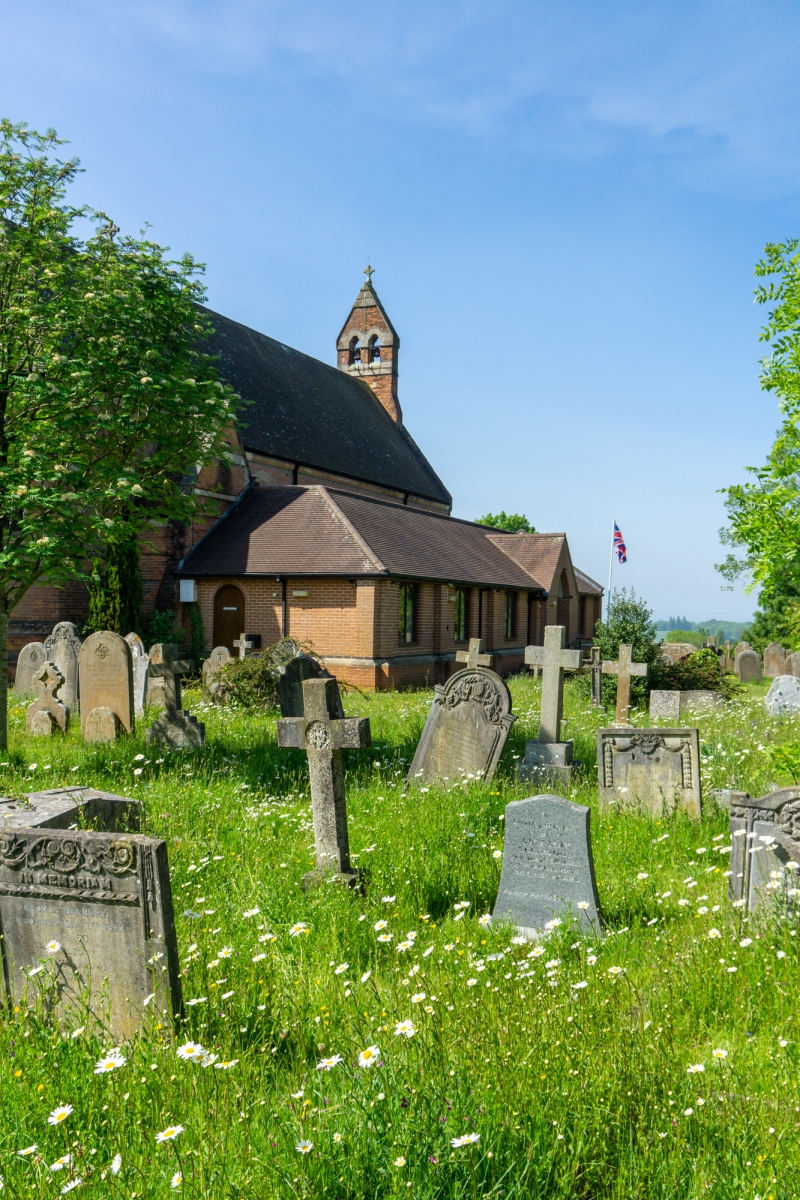 St. Mark's churchyard, showing gravestones, wildflowers and the union flag on a flagpole.