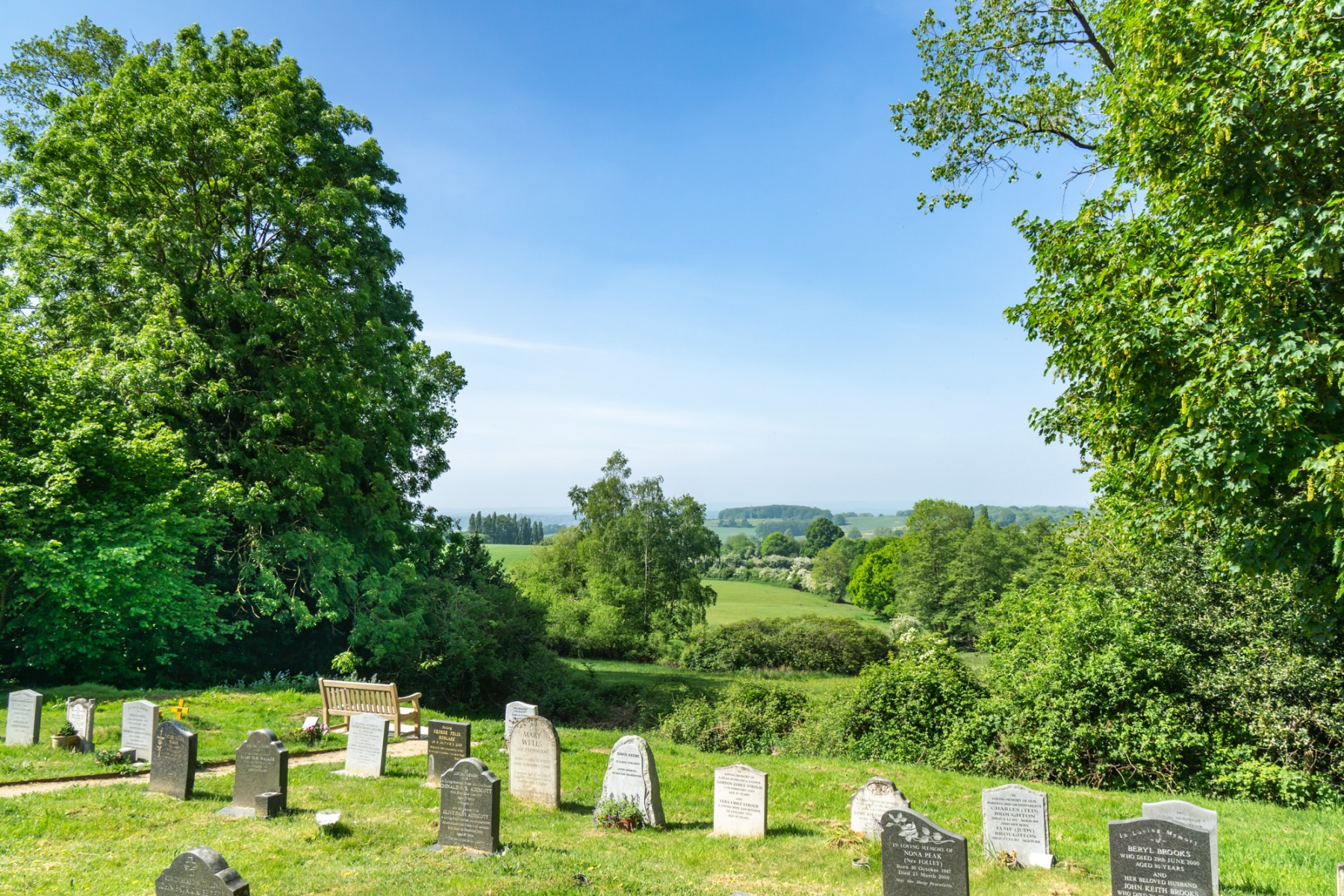 A rolling countryside view from the rear of the church. Gravestones and a bench can be viewed in the foreground.