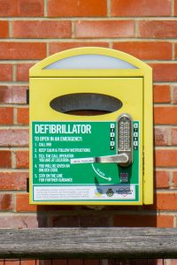 A yellow defibrillator cabinet is attached to a brick wall.