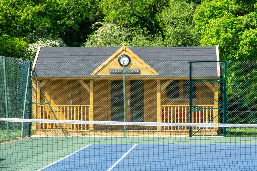 The tennis club pavilion is made of wood with grey roof tiles. A clock is visible on the front.